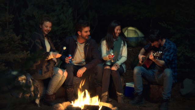 Young adults with a guitarre and Pepsi around a campfire in the publicity Contradiction from Pepsi, directed by Yan Giroux with Alt productions